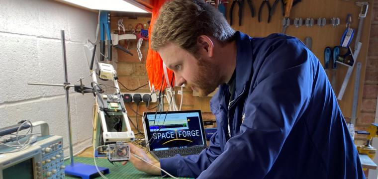 Space Forge co-founder Andrew Bacon working in garage